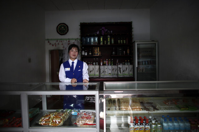 A vendor stands inside a shop at the North Korean Special Economic Zone of Rason City in Rajin, northeast of Pyongyang August 29, 2011. (Photo by Carlos Barria/Reuters)
