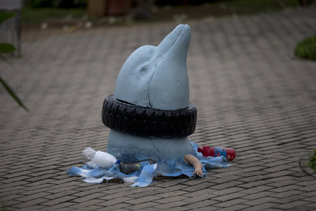 A sculpture of a dolphin with a tire caught around its neck is exhibited at Rio de Janeiro Federal University as part of the exhibit titled The Sea Isnt Made for Fish, in Rio de Janeiro, Brazil, Monday, June 1, 2015. Art students have taken advantage of a material they have in endless supply trash to create an exhibition that aims to draw attention to the fetid state of the citys Guanabara Bay, where the Olympic sailing events are to be held next year. (AP Photo/Silvia Izquierdo)