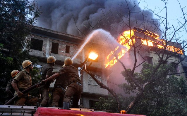Firefighters hold a hosepipe to douse flames as a fire has broken out in a multi-storey commercial building at Chandni Chowk in Kolkata on June 16, 2019. (Photo by AFP Photo/Stringer)
