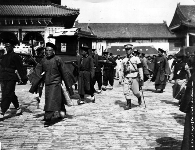 1908: The Dalai Lama of Tibet, being carried in his sedan chair, attending the funeral of the Dowager Empress of China