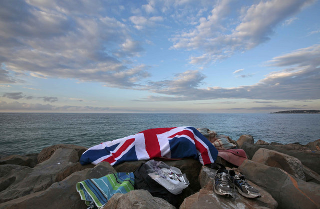 A migrant sleeps covered by an Union-Jack flag on the rocks of the seawall at the Saint Ludovic border crossing on the Mediterranean Sea between Vintimille, Italy and Menton, France, June 17, 2015. On Saturday, some 200 migrants, principally from Eritrea and Sudan, attempted to cross the border from Italy and were blocked by Italian police and French gendarmes.    REUTERS/Eric Gaillard  TPX IMAGES OF THE DAY