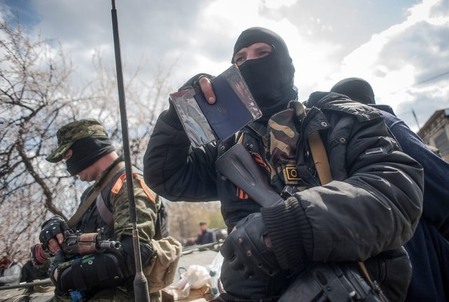 An armed man shows his Ukrainian passport as he stands near of tanks (behind, not seen) in Slaviansk, Ukraine, 16 April 2014. According to media reports, about six armored vehicles which were seized by armored pro-Russian men in military uniform in Kramatorsk, arrived to the eastern Ukrainian town of Slaviansk. (Photo by Roman Pilipey/EPA)