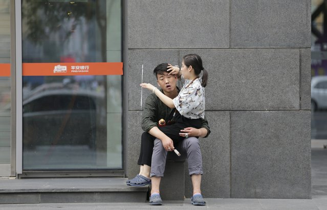 A couple rest outside the branch of Ping An Bank in Beijing's central business district, June 25, 2015. (Photo by Jason Lee/Reuters)