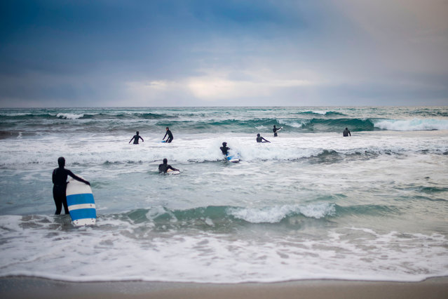 Novice surfers learn how to ride a wave in Unstad along the northern Atlantic Ocean on March 12, 2017, where the water temperatures is at five degrees centigrade and the air temperature is at minus two degrees centigrade. (Photo by Olivier Morin/AFP Photo)