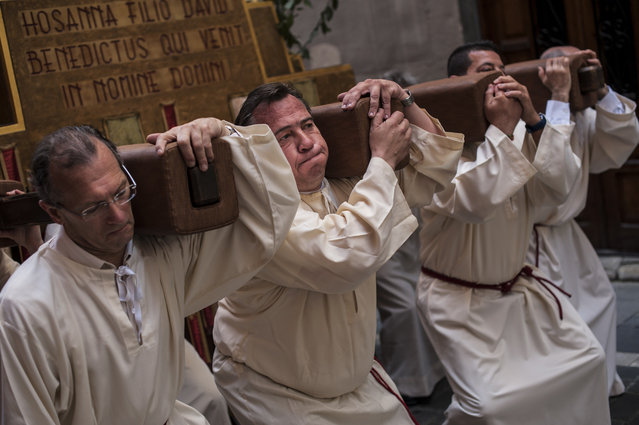 Penitents take part in the procession during Palm Sunday, prior to Spain Holy Week, in Pamplona, northern Spain, Sunday April 13, 2014. Spanish devoted Catholics take part in a lot of religious ceremonies during Holy Week. (Photo by Alvaro Barrientos/AP Photo)