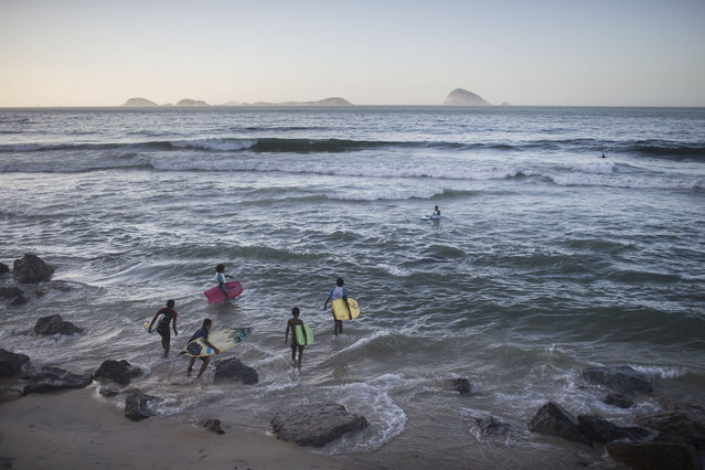 In this  May 21, 2015 photo, young surfers from the Rocinha slum enter the water at Sao Conrado beach in Rio de Janeiro, Brazil. Everyday barefoot boys hustle down the inclined alleyways of the Rio de Janeiro slums they call home, surf boards under their arms. They head to nearby Sao Conrado or Arpoador beach, where they catch waves and momentarily leave their impoverished lives behind. (Photo by Felipe Dana/AP Photo)