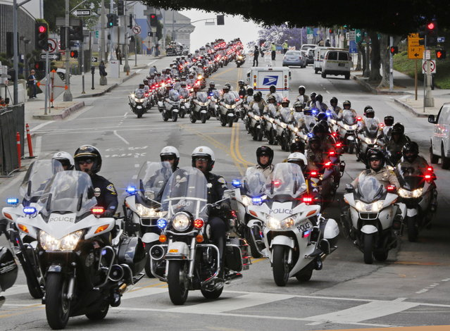 A procession of motorcycle officers leads the hearse carry the coffin of Los Angeles Police Dept. motorcycle officer Chris Cortijo after a funeral service at the Cathedral of Our Lady of the Angels Tuesday morning, April 22, 2014, in Los Angeles. Hundreds of fellow law enforcement officers turned out to mourn 51-year-old officer, who who died after he struck by a motorist allegedly under the influence of cocaine on April 5. (Photo by Damian Dovarganes/AP Photo)