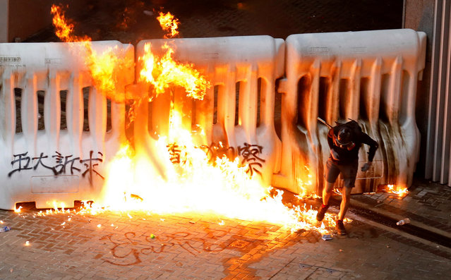 A demonstrator runs away from a burning barricade during a protest in Hong Kong, China, August 31, 2019. (Photo by Anushree Fadnavis/Reuters)