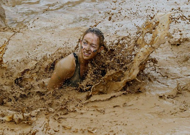 A participant jumps into the mud as she takes part in the Mud Day athletic event in Beynes, west of Paris, France, Saturday, May 7, 2016. Thousands of runners seeking an athletic challenge are competing in a circuit of approximately 13 kilometers (8 miles) with over 20 obstacles, some of them set in mud. (Photo by Michel Euler/AP Photo)