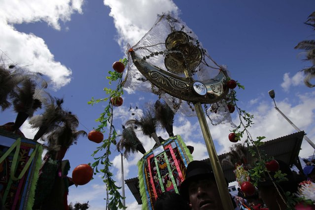 """In this June 7, 2015 photo, a steward or """"prioste"""" carries a staff or """"Guion"""", depicting a mixture of Catholic and indigenous symbols, during the celebration of Corpus Christi or Danzante de Pujili, in Pujili, Ecuador. The crescent of the Guion is engraved with a variety of symbols and a mirror embedded in its center. The Guion is also garnished with jewelry and ribbons, and topped with a crucifix, symbolizing the region's cultural heritage. (Photo by Dolores Ochoa/AP Photo)"""