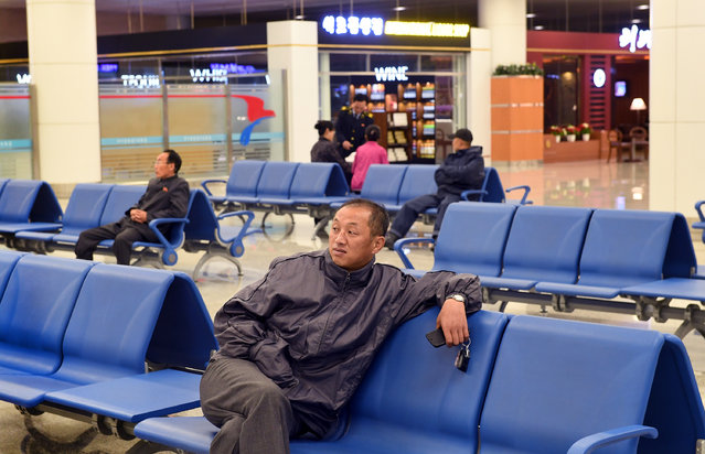 A korean man waits at the main airport in Pyongyang, North Korea on May 3, 2016. The newly renovated airport sports liquor and coffee shops, numerous restaurants and a bright interior. (Photo by Linda Davidson/The Washington Post)