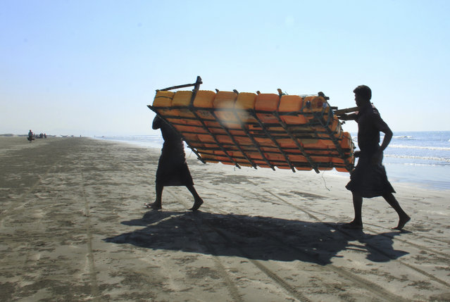 In this January 16, 2017, photo, Rohingya fishermen carry a fishing raft, constructed with empty plastic containers, up the beach in Tha Pyay Taw village, Maungdaw, western Rakhine state, Myanmar. (Photo by Esther Htusan/AP Photo)