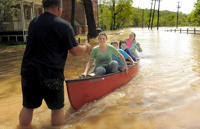 Freddie Jent,left, of Fredericksburg, Va, gives his children Mary Jent, William Jent, Rachel Jent, and Wendy Jent a ride in a canoe along the flooded King Street (River Road) in historic Falmouth, Va, May 1, 2014. Freddie Jent's father's house was flooded just down the road. The Rappahannock River crested at 22 feet. (Photo by Suzanne Carr-Rossi/AP Photo/The Free Lance-Star)