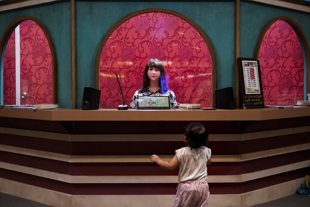 A baby girl looks at a humanoid robot sitting in a box office Friday, August 23, 2019, in Tokyo. (Photo by Jae C. Hong/AP Photo)