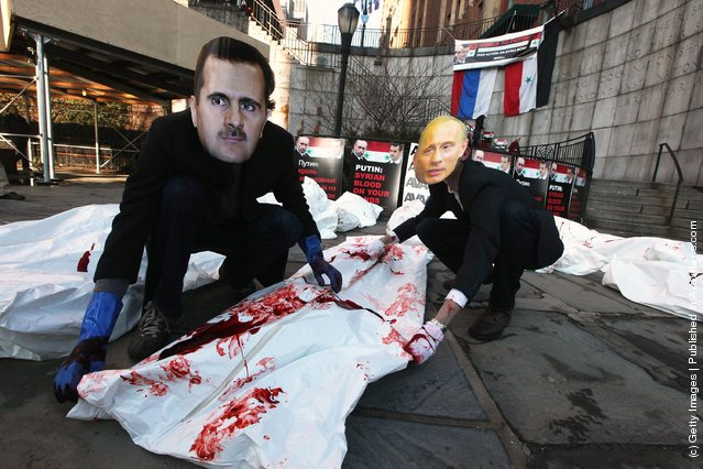 Actors wearing masks of Syrian President Bashar al-Assad and Russian Prime Minister Vladimir Putin perform with body bags during a demonstration outside United Nations headquarters