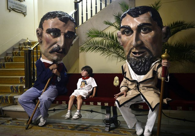 "A boy sits between two ""Cabezudos"" (big headed figures) at the City Hall of Pamplona, Spain, July 14, 2015, during the last day of the San Fermin Festival. The festival is a symbol of Spanish culture that attracts thousands of tourists. (Photo by Miguel Riopa/AFP Photo)"