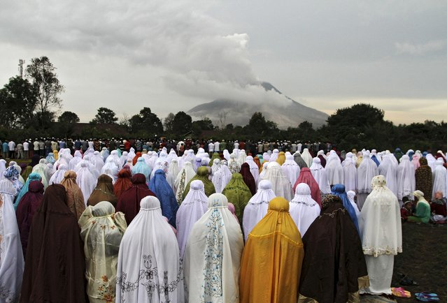 Displaced Muslims living near the active volcano Mount Sinabung take part in an Eid al-Fitr prayer near the volcano at Ndokum Siroga village in Karo, North Sumatra Indonesia, July 17, 2015. Indonesia, which has the world's largest Muslim population, celebrates Eid al-Fitr with mass prayers and family visits to mark the end of the holy fasting month of Ramadan. (Photo by Y. T Haryono/Reuters)