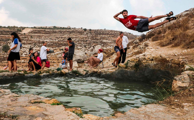 Israelis sit by as a man poses while jumping into the pool of the natural water spring of Ein al-Faraah near the Palestinian village of Doura, west of Hebron in the occupied West Bank, during the Jewish religious holiday of Sukkot (Feast of the Tabernacles) on October 17, 2019. (Photo by Hazem Bader/AFP Photo)
