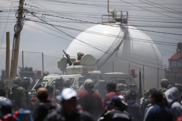 Soldiers guard the perimeters of the state-own Senkata filling plant, as supporters of former President Evo Morales gather round, in El Alto, on the outskirts of La Paz, Bolivia, Tuesday, November 19, 2019. Morales' backers have taken to the streets asking for his returns since he resigned on Nov. 10 under pressure from the military after weeks of protests against him over a disputed election he claim to have won. (Photo by Natacha Pisarenko/AP Photo)