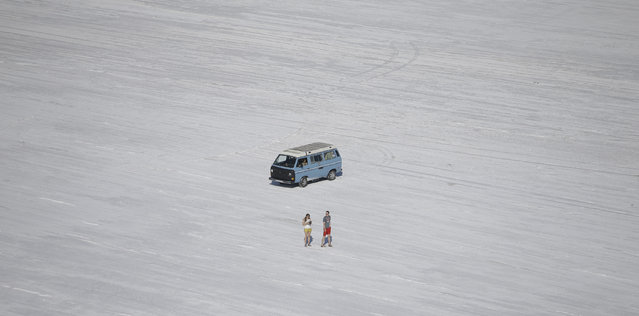 In this Wednesday, July 22, 2015 photo, a couple walks on the Bonneville Salt Flats, in Utah. A small city of tents, trailers and thousands of visitors appears almost every August in the Utah desert to watch cars, motorcycles and anything with wheels rocket across gleaming white sheets of salt at speeds of 400 mph. (Photo by Rick Bowmer/AP Photo)