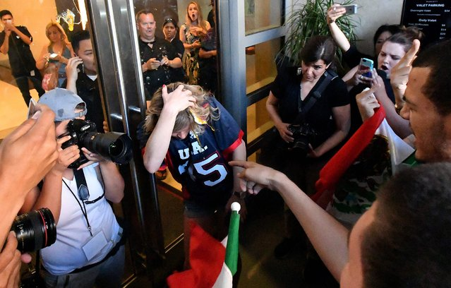 A woman wearing a Trump shirt (C) is pelted with eggs by protesters while pinned against a door near where Republican presidential candidate Donald Trump holds a rally in San Jose, California on June 02, 2016. Protesters attacked Trump supporters as they left the rally, burned an american flag, trump paraphernalia and scuffled with police and each other. (Photo by Josh Edelson/AFP Photo)