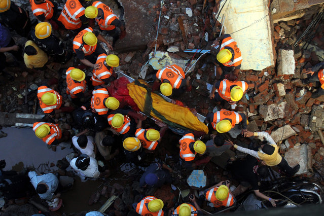 Rescuers carryt he dead body of a victim killed in a building collapse near Thakurli railway station in Thane near Mumbai, India, 29 July 2015. Nine people have died in a building collapse in India's Maharashtra state and several others are feared trapped in the rubble, police said on 29 July. The three-storey building collapsed on 28 July night during heavy rains, said Dilip Wagle, an official at the police control room in Maharashtra state's Thane district. (Photo by EPA/Stringer)