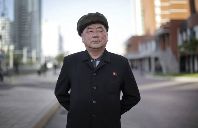"""In this May 7, 2016, photo, Pak Su Won, 66, a retired local physician, poses for a portrait along Mirae Scientists Street in Pyongyang, North Korea. His motto: """"To devote myself to leader Kim Jong Un for the rest of my life. For him, and for the fatherland"""". (Photo by Wong Maye-E/AP Photo)"""