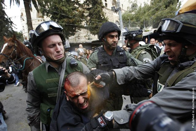 Israeli border police officers use pepper spray as they detain an injured Palestinian protester during clashes on Land Day after Friday prayers outside Damascus Gate in Jerusalem's Old City, March 30. Israeli security forces fired rubber bullets, tear gas and stun grenades to break up groups of Palestinian stone-throwers as annual Land Day rallies turned violent