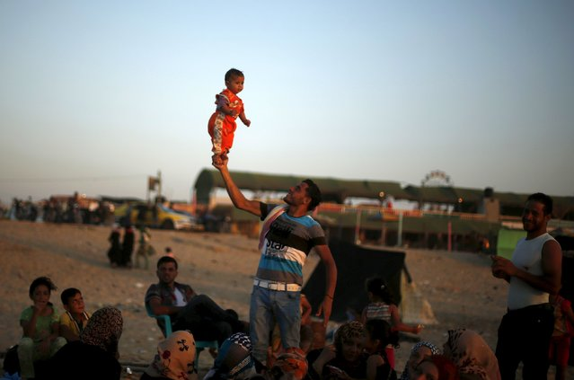 A Palestinian man lifts his daughter as he enjoys the warm weather with his family on a beach along the Mediterranean Sea in the northern Gaza Strip July 24, 2015. (Photo by Mohammed Salem/Reuters)