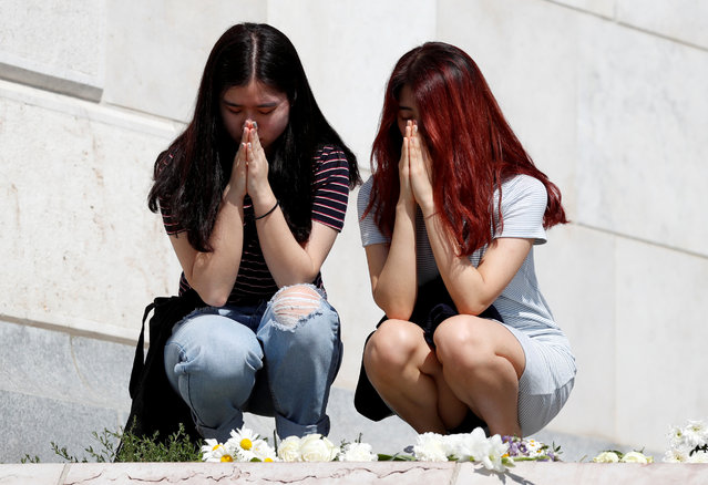 Women pray to mourn the victims of a ship accident, which killed several people on the Danube river, in Budapest, Hungary, May 31, 2019. (Photo by Bernadett Szabo/Reuters)