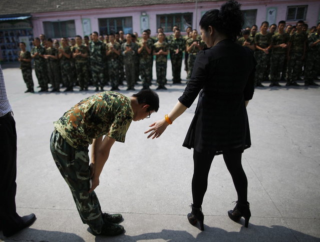 A student who has completed a six months course bows to the head teacher at the Qide Education Center in Beijing June 11, 2014. (Photo by Kim Kyung-Hoon/Reuters)