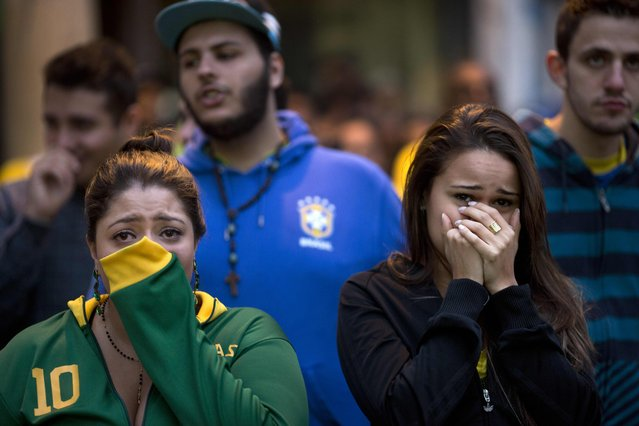 Brazil soccer fans watch their team lose to Germany in a World Cup semifinal game on TV in Sao Paulo, Brazil, Tuesday, July 8, 2014. (Photo by Rodrigo Abd/AP Photo)
