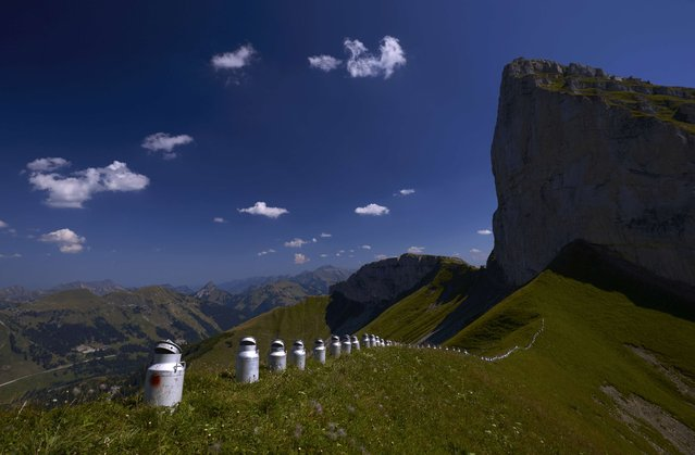 "An art installation formed with milk churns, made by land art artist Gerard Benoit a la Guillaume, is seen at the Chenau de Mayen in the resort of Leysin, Switzerland August 7, 2015. More than 80 milk churns were placed between the Tour d'Ai and the Tour de Mayen summits at an altitude of 2,000 meters (6,561 feet) above sea level under the direction of the artist, to be photographed for his ongoing art project entitled ""Milk churns without borders"". (Photo by Denis Balibouse/Reuters)"