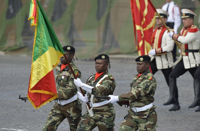 Congolese and Macedonian (R) soldiers march down the Champs-Elysees avenue in Paris during the annual Bastille Day military parade on July 14, 2014. France has issued an unprecedented invitation to all 72 countries involved in World War I to take part in its annual Bastille Day military parade. (Photo by Miguel Medina/AFP Photo)