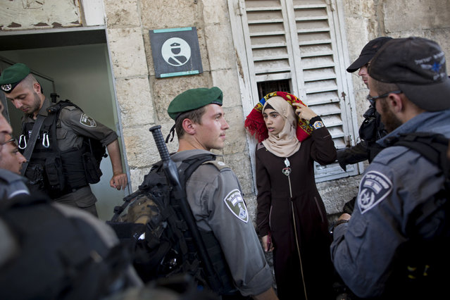 Israeli border police officers stop a Palestinian woman for a security check as Palestinians gather for prayer at the Lion's Gate, following an appeal from clerics for Muslims to pray in the streets instead of the Al-Aqsa Mosque compound, in Jerusalem's Old City, Wednesday, July 19, 2017. A dispute over metal detectors has escalated into a new showdown between Israel and the Muslim world over the contested Jerusalem shrine that has been at the center of violent confrontations in the past. (Photo by Oded Balilty/AP Photo)