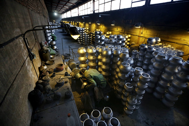 An Afghan laborer makes cooking pots made out of aluminum at a factory, on the outskirts of Kabul, Afghanistan, Tuesday, August 4, 2015. (Photo by Rahmat Gul/AP Photo)