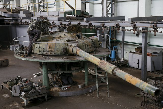 An employee works on a tank turret as armored vehicles are repaired at the Kiev armored plant, Ukraine, August 14, 2015. (Photo by Valentyn Ogirenko/Reuters)