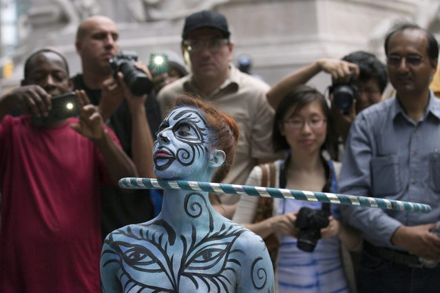 A model hula hoops after being painted as spectators stand near at Columbus Circle as body-painting artists gathered to decorate nude models as part of an event featuring artist Andy Golub, Saturday, July 26, 2014, in New York. Golub says New York was the only city in the country that would allow his inaugural Bodypainting Day. (Photo by John Minchillo/AP Photo)