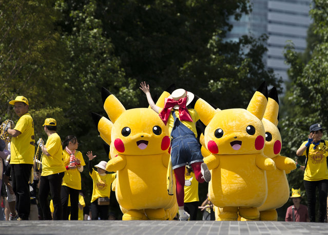 Performers dressed as Pikachu, a character from Pokemon series game titles, march during the Pikachu Outbreak event hosted by The Pokemon Co. on August 9, 2017 in Yokohama, Kanagawa, Japan. (Photo by Tomohiro Ohsumi/Getty Images)
