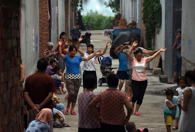 A group of women take part in an early morning dance session, as villagers look on, in Weijian village, in China's Henan province on July 30, 2014. Group dancing and exercise are popular activities in villages across the country. (Photo by Greg Baker/AFP Photo)