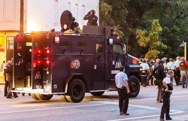 Police watch from an armoured car as protesters gathered after a shooting incident in St. Louis, Missouri August 19, 2015. (Photo by Kenny Bahr/Reuters)