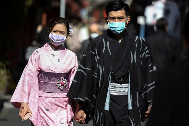 Tourists wearing kimono and protective masks visit Sensoji Temple in Asakusa district in Tokyo, Japan, February 18, 2020. (Photo by Athit Perawongmetha/Reuters)