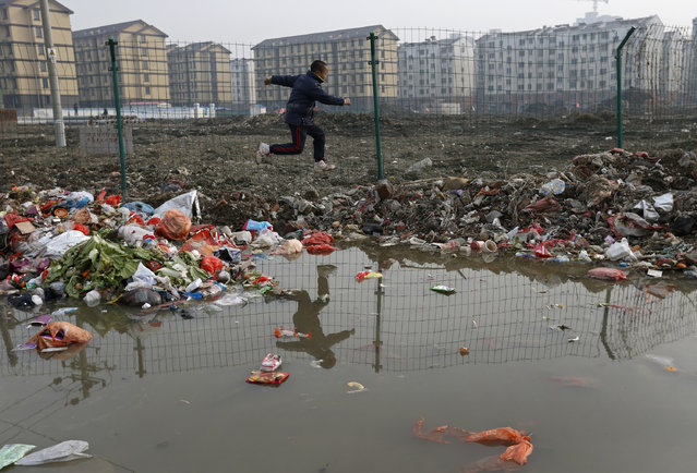 A child is reflected in a drainage ditch as he jumps over trash at a village which will soon be demolished, on the outskirts of Jiaxing city, Zhejiang province, January 12, 2013. New residential buildings are seen in the background. (Photo by William Hong/Reuters)