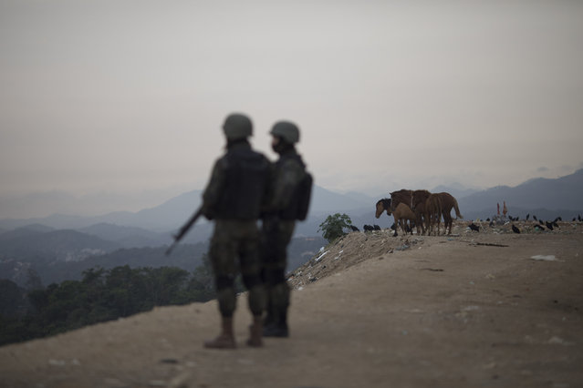 Air force personnel patrol on a landfill at the Caramujo slum in Niteroi, Brazil, Wednesday, August 16, 2017. Thousands of soldiers and police began patrolling metropolitan region of Rio de Janeiro as part of security actions to diminish the violence in the state. (Photo by Leo Correa/AP Photo)