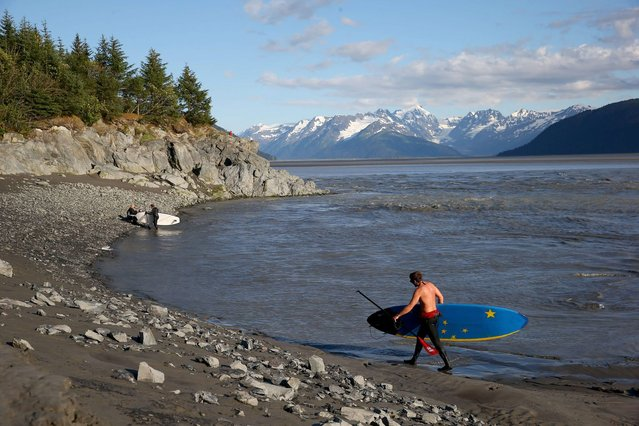 Surfers pack up for the day along the Seward highway after surfing the Bore Tide at Turnagain Arm on July 14, 2014 in Anchorage, Alaska. Alaskas most famous Bore Tide, occurs in a spot on the outside of Anchorage in the lower arm of the Cook Inlet, Turnagain Arm, where wave heights can reach 6-10 feet tall, move at 10-15 mph and the water temperature stays around 40 degrees farenheit. This years Supermoon substantially increased the size of the normal wave and made it a destination for surfers. (Photo by Streeter Lecka/Getty Images)