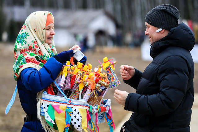 A woman selling effigies of winter during a celebration of Maslenitsa festival (Pancake Week) at the Etnomir (Ethnoworld) cultural and educational center in Kaluga Region, Russia on March 1, 2020. The holiday celebrates the end of winter and marks the arrival of spring. (Photo by Sergei Bobylev/TASS)