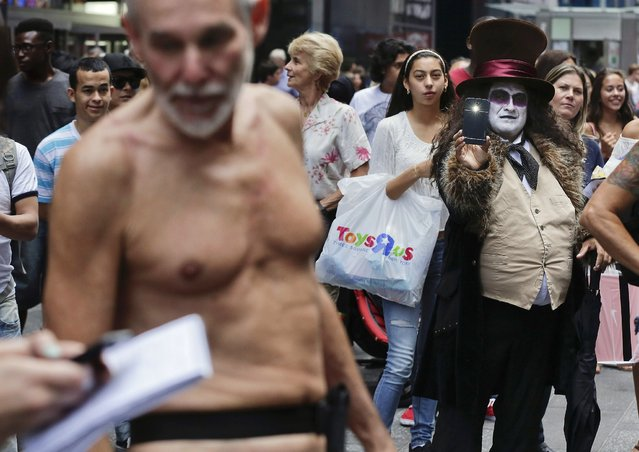 """An entertainer dressed as the Penguin character from the comic book series """"Batman"""" shoots photos of George Davis who walked through Times Square in the nude after giving a speech, Wednesday, August 6, 2014, in New York. Davis, a candidate for the San Francisco Board of Supervisors, spoke out against a 2013 San Francisco public nudity ban that was introduced by his opponent, Scott Wiener, saying nudity is a freedom of expression. (Photo by Julie Jacobson/AP Photo)"""
