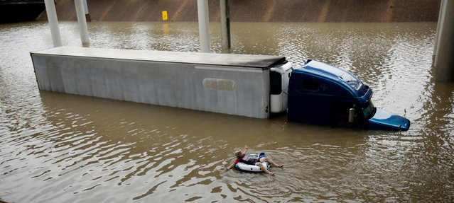 After helping the driver of the submerged truck get to safety, a man floats on the freeway flooded by Tropical Storm Harvey on Sunday, August 27, 2017, near downtown Houston. (Photo by Charlie Riedel/AP Photo)