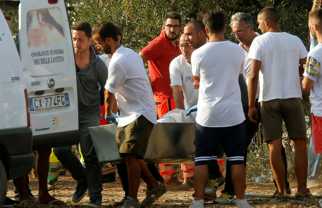 Rescuers carry a coffin at the site where two passenger trains collided in the middle of an olive grove in the southern village of Corato, near Bari, Italy, July 12, 2016. (Photo by Alessandro Garofalo/Reuters)