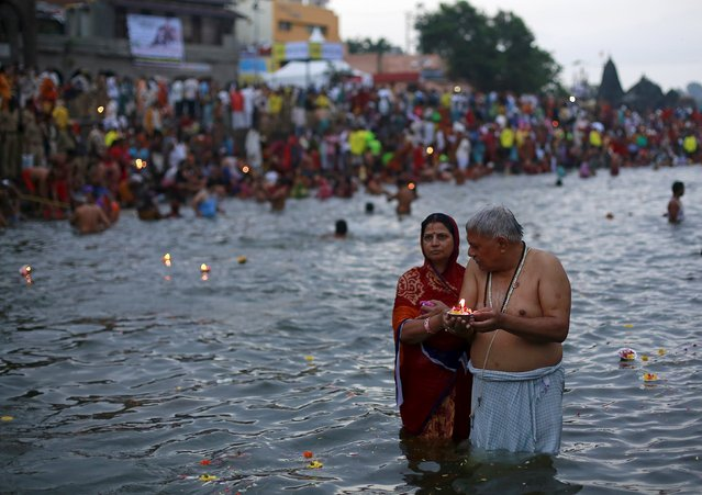 Hindu devotees pray while standing in the Godavari river during Kumbh Mela or the Pitcher Festival in Nashik, India, August 26, 2015. Hundreds of thousands of Hindus took part in the religious gathering at the banks of the Godavari river in Nashik city at the festival, which is held every 12 years in different Indian cities. (Photo by Danish Siddiqui/Reuters)